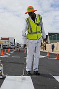 Een wegwerker verft de nieuwe wegmarkering, WK 2010 Zuid Afrika
