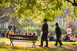 © Licensed to London News Pictures; 12/09/2020; Bristol, UK. Two police officers are seen in St Andrews Park, where large groups of young people are enjoying the early evening sunshine on the last weekend before new restrictions for the coronavirus covid-19 pandemic come into law in England. From Monday 14 September it will be illegal to meet up in groups of more than six people, known as the rule of six, in order to try and contain the spread of the coronavirus. Yesterday Bristol recorded the biggest daily increase in 10 weeks of new cases of coronavirus, and nationally, 3,539 new cases have been confirmed, the highest rise for four months. Photo credit: Simon Chapman/LNP.