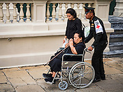 29 OCTOBER 2016 - BANGKOK, THAILAND: Thai military medic helps a woman in a wheelchair go into the Grand Palace to pay homage to the late Thai King. Saturday was the first day Thais could pay homage to the funeral urn of the late Bhumibol Adulyadej, King of Thailand, at Dusit Maha Prasart Throne Hall in the Grand Palace. The Palace said 10,000 people per day would be issued free tickerts to enter the Throne Hall but by late Saturday morning more than 100,000 people were in line and the palace scrapped plans to require mourners to get the free tickets. Traditionally, Thai Kings lay in state in their urns, but King Bhumibol Adulyadej is breaking with tradition. His urn reportedly contains some of his hair, but the King is in a coffin,  not in the urn. The laying in state will continue until at least January 2017 but may be extended.       PHOTO BY JACK KURTZ