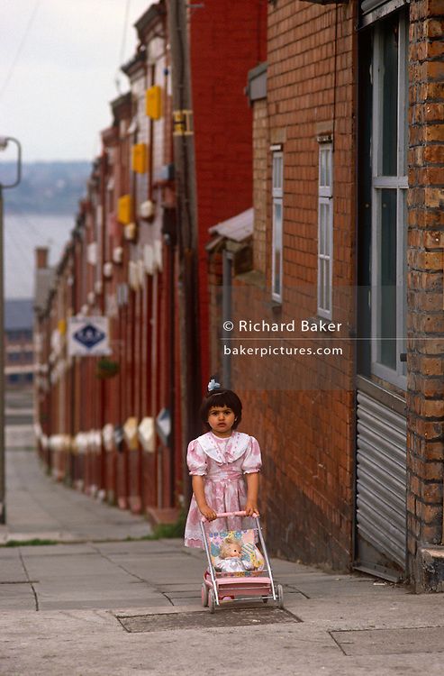 A young girl of Asian descent pushes her doll in a pushchair uphill in an empty terraced Dingle Liverpool street. Walking up the steep pavement she pauses to look at the viewer in her pink dress. There is no-one else in the landscape and the little girl is quite alone in this inner-city scene. Dingle (known locally as the Dingle) is an inner-city area of Liverpool, Merseyside, England. It is located to the south of the city, bordered by the adjoining districts of Toxteth and Aigburth. At the 2001 Census, the population was recorded at 13,246. Dingle is the last of the southern inner-city districts of Liverpool.