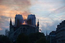 Bystanders look on as flames and smoke are seen billowing from the roof at Notre-Dame Cathedral with sunset and a plane passing by in Paris on April 15, 2019. A fire broke out at the landmark Notre-Dame Cathedral in central Paris, potentially involving renovation works being carried out at the site, the fire service said.Images posted on social media showed flames and huge clouds of smoke billowing above the roof of the gothic cathedral, the most visited historic monument in Europe. Photo by Raphael Lafargue/ABACAPRESS.COM