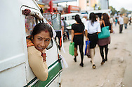 Rukpa Karki, 31, waits for passengers to fill her tempo, a three-wheeled minibus, in Kathmandu, Nepal. Karki has been a tempo driver for 10 years, a profession in Nepal held by men and women.