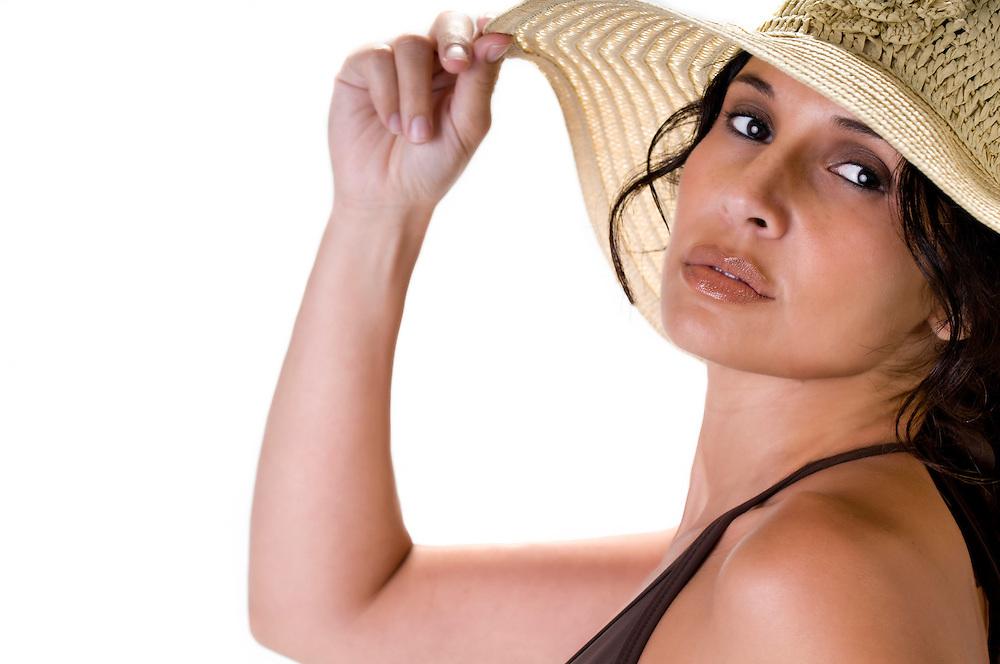 Portrait of hispanic woman wearing beach hat, looking at camera.
