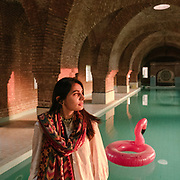 Rabeeya Arif, a graduate of NCA, stands near the indoor swimming pool at the Harsukh art community in Lahore. The pool was designed to resemble a traditional Turkish bath, or hammam.