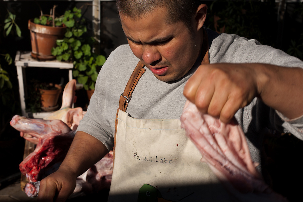 Antonio Villagomez, head chef and owner of Cilantros Restaurant in Yuba City, California, butchers a whole pig at his home in Yuba City.
