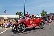 The Millville Community Fire Company clowns drive an antique car in the Independence Day parade in Millville, Pennsylvania on July 5, 2021.
