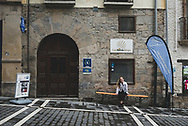 Anna, a pilgrim from the United States, sits outside Casa Ibarrola Albergue, where she overnighted in Pamplona, Spain. (June 1, 2018)<br />