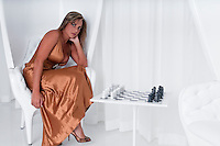 Young woman waiting for her partner to play a chess game in upscale location.