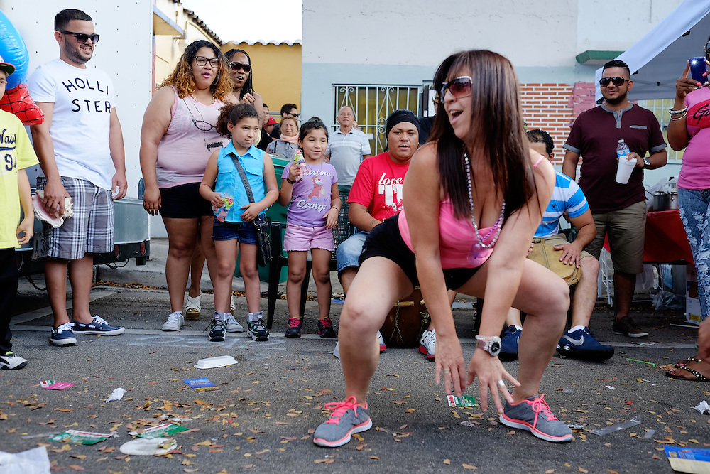 MIAMI - MARCH 9, 2014: Portrait of woman dancing in the streets during the 37th Calle Ocho festival, an annual event that takes place over Eight Street in Little Havana featuring plenty of music, food, and  it is the biggest party in town that celebrates hispanic heritage.