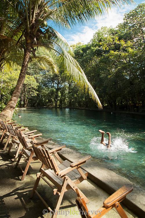 Man diving into Ojo de Agua spring on Ometepe Island, Nicaragua