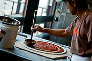 """SHOT 8/10/09 5:31:51 PM - Making a pizza at Fat Sully's New York Style PIzza on Colfax Avenue in Denver, Co. Colfax Avenue is the main street that runs east and west through the Denver-Aurora metropolitan area in Colorado. As U.S. Highway 40, it was one of two principal highways serving Denver before the Interstate Highway System was constructed. In the local street system, it lies 15 blocks north of the zero point (Ellsworth Avenue, one block south of 1st Avenue). For that reason it would normally be known as """"15th Avenue"""" but the street was named for the 19th-century politician Schuyler Colfax. On the east it passes through the city of Aurora, then Denver, and on the west, through Lakewood and the southern part of Golden. Colloquially, the arterial is referred to simply as """"Colfax"""", a name that has become associated with prostitution, crime, and a dense concentration of liquor stores and inexpensive bars. Playboy magazine once called Colfax """"the longest, wickedest street in America."""" However, such activities are actually isolated to short stretches of the 26-mile (42 km) length of the street. Periodically, Colfax undergoes redevelopment by the municipalities along its course that bring in new housing, trendy businesses and restaurants. Some say that these new developments detract from the character of Colfax, while others worry that they cause gentrification and bring increased traffic to the area. (Photo by Marc Piscotty / © 2009)"""