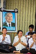 "01 FEBRUARY 2013 - PHNOM PENH, CAMBODIA: Mourners with a photo of former King Sihanouk on Sisowath Quay, Phnom Penh's riverfront boulevard, watch the funeral procession of former King Norodom Sihanouk. Norodom Sihanouk (31 October 1922 - 15 October 2012) was the King of Cambodia from 1941 to 1955 and again from 1993 to 2004. He was the effective ruler of Cambodia from 1953 to 1970. After his second abdication in 2004, he was given the honorific of ""The King-Father of Cambodia."" Sihanouk died in Beijing, China, where he was receiving medical care, on Oct. 15, 2012. His cremation is will be on Feb. 4, 2013. Over a million people are expected to attend the service.    PHOTO BY JACK KURTZ"
