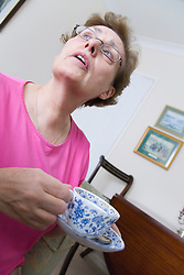 Older woman sitting at home drinking a cup of tea,