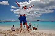 Bar waitress, from the Carnival Cruise Lines,  jumps in the beach of Half Moon Cay, Bahamas.