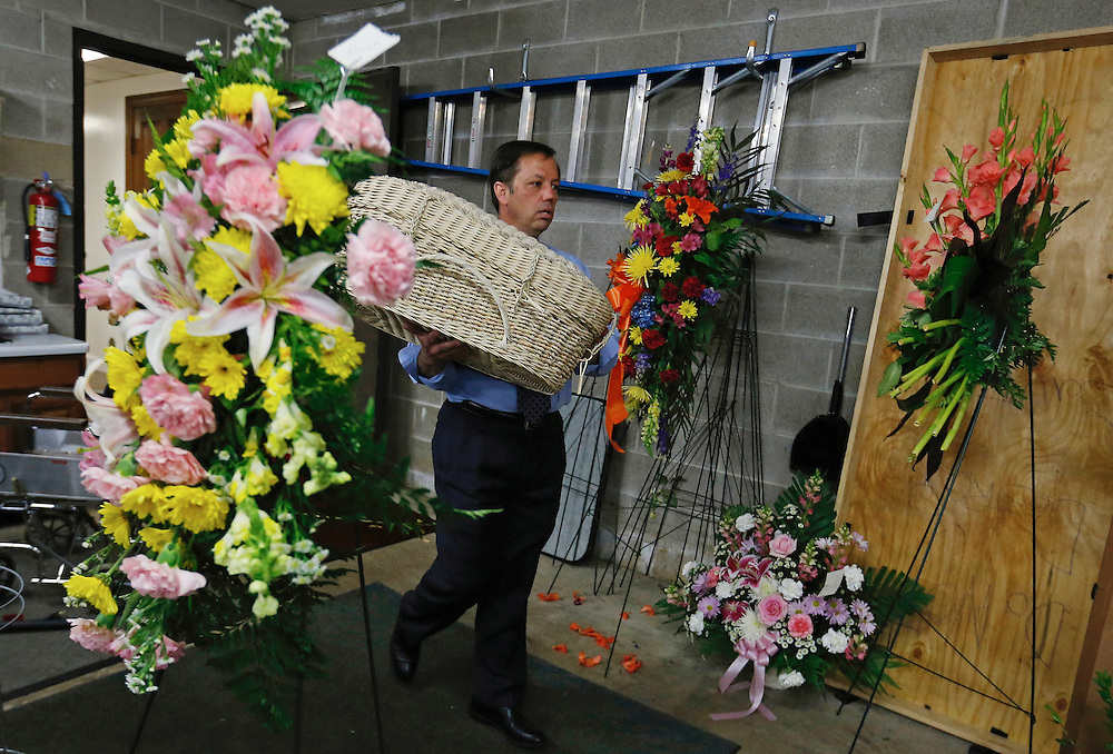 """Glueckert Funeral Home Funeral director John Glueckert carries a bassinet to the hearse as he prepares to go to the Cook County Medical Examiner's to claim the remains of an abandoned baby in Arlington Heights, Illinois, United States, June 11, 2015. More than a year after he was found dead in a plastic shopping bag on a Chicago sidewalk, Glueckert and a non-profit group """"Rest in His Arms"""" stepped in to provide funeral and burial services for the baby boy. The teenage mother is charged with murder. REUTERS/Jim Young"""
