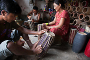 A small drum making factory in Dhading run by husband and wife, assisted by their nephew. The drums are made of wood and mountain goat intestines and fine tuned using black carbon rock. The drum comes in different sizes and is a traditional instrument in Nepal used on many occations.