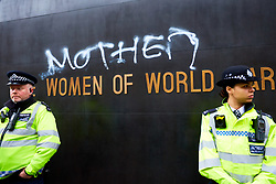 © Licensed to London News Pictures. 24/11/2018. LONDON, UK.  Graffiti reading 'Mother' is spray painted into The Women of World war II memorial in Whitehall during a protest by Extinction Rebellion. The man responsible was quickly stopped by police and detained. The group is conducting a campaign of civil disobedience to highlight the urgency of action on climate change and species loss.  Photo credit: Cliff Hide/LNP