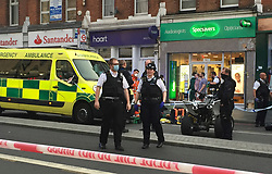 © Licensed to London News Pictures. 21/07/2021. London, UK. Police officers and ambulance medics are seen at a fatal stabbing in Brixton, south London. An investigation is underway after a man died following a stabbing in Brixton. Police were called at 20:18hrs on Wednesday, 21 July to reports of an assault close to Brixton Underground Station. Officers attended and found a man, believed to be aged in his early 20s, suffering from a stab injury. They immediately provided first aid. The London Ambulance Service and London's Air Ambulance also attended but despite their efforts the man was pronounced dead at the scene at the 20:45hrs. His next of kin has been informed and are being supported by officers. Formal identification has not taken place. A man was arrested nearby on suspicion of causing grievous bodily harm. Photo credit: Andy Gatt/LNP