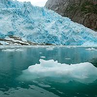 A glacier icefall in the Cordillera Darwin flows into Seno Chico, a small, icy fjord in Alberto de Agostini National Park, Tierra del Fuego, Chile.