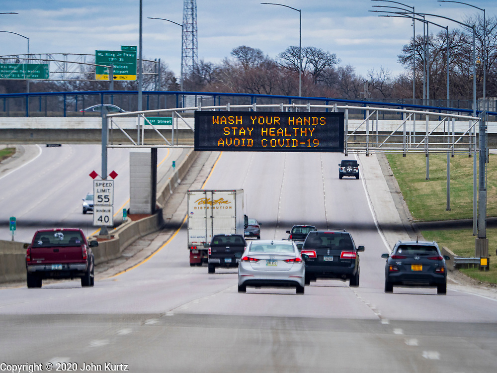 """29 MARCH 2020 - DES MOINES, IOWA: A road sign that normally displays traffic safety messages displays a COVID-19 safety message over I-235 eastbound in downtown Des Moines. On Sunday morning, 29 March, Iowa reported 336 confirmed cases of the Novel Coronavirus (SARS-CoV-2) and COVID-19. There have been four deaths attributed to COVID-19 in Iowa. Restaurants, bars, movie theaters, places that draw crowds are closed until 07 April. The Governor has not ordered """"shelter in place""""  but several Mayors, including the Mayor of Des Moines, have asked residents to stay in their homes for all but the essential needs. People are being encouraged to practice """"social distancing"""" and many businesses are requiring or encouraging employees to telecommute.         PHOTO BY JACK KURTZ"""