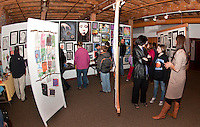 Winnisquam Regional Middle School art teacher Jessica Cobbett (far right) chats with visitors at they meander through the various displays presented at the Arts Alive event Thursday evening at the Belknap Mill.  (Karen Bobotas/for the Laconia Daily Sun)