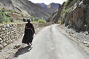 India, Jammu and Kashmir, Ladakh, Local woman walks in the landscape
