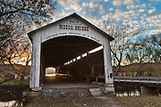 """Mecca Covered Bridge (150 feet long) was built in Burr Arch style over Big Raccoon Creek in 1873 by J.J. Daniels in historic Parke County, Indiana, USA. Golden sunset light beckons at the far opening. Puffy white clouds decorate the blue sky. The traditional """"Cross this bridge at a walk"""" sign required slow vehicle speed, but traffic is now diverted to an adjacent modern bridge."""