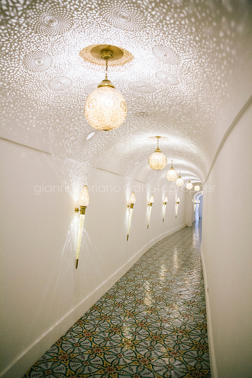 POSITANO, ITALY - 13 SEPTEMBER 2018: A view of the corridor with fine art lamps from Marrakesh is seen here at Villa Tre Ville in Positano, Italy, on September 13th 2018.<br /> <br /> Villa Tre Ville was originally purchased in the 1920s by the Russian writer Mikhail Semenov. Later purchased by the Italian film and opera director Franco Zeffirelli in the 1960s, the property was often visited by dancers, singers, writers, musicians, painters, actors and intellectuals from all over the globe. Among these artists were Liz Taylor, Maria Callas, Leonard Berstein, Laurence Olivier. In 2007 the villa was sold to the hotelier Giovanni Russo. In 2013 Robert Friedland announced that the company's Ivanhoe Italia LLC subsidiary has completed the acquisition of the Villa Tre Ville and that it  would form part of an Ivanhoe group of international boutique hotels and villas, with other locations under development in Thailand and Japan.