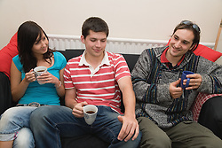 Group of friends in a shared house relaxing on the sofa,