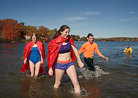 "Jill Dennis and Emily Lamot of the ""Super Heros Team"" come out of the water at Lake Opechee during the 11th annual Turkey Plunge for the Salvation Army on Saturday afternoon.  (Karen Bobotas/for the Laconia Daily Sun)"