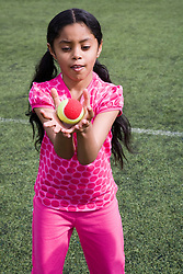 Young girl trying to catch a tennis ball in a game at her local leisure centre,