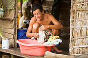 28 JUNE 2006 - CHONG KHNEAS, SIEM REAP, CAMBODIA: A man does his laundry on his home in the floating village of Chong Khneas, at the northwest end of Tonle Sap Lake, Cambodia's vast inland sea. More than 2,500 people live on the lake in houses that move as the lake expands and contracts with the seasons. During the dry season the lake covers about 2,500 square kilometers. At the peak of the rainy season the Tonle Sap swells to more than 13,000 square kilometers. Photo by Jack Kurtz