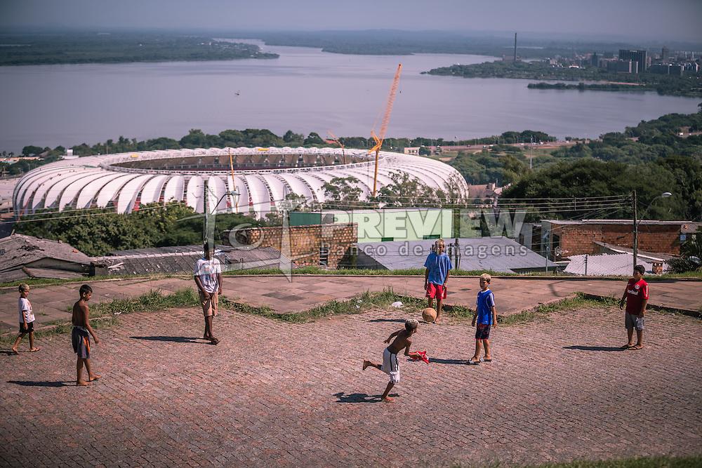 Crianças jogam futebol com o estádio Beira Rio ao fundo, em 31 de fevereiro de 2014. O Estádio Beira Rio, que receberá jogos da Copa do Mundo de Futebol 2014, tem mais 97% da sua reforma concluída e re-inauguração agendada para 04 de abril de 2014. FOTO: Jefferson Bernardes/ Agência Preview