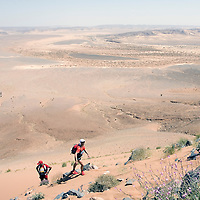 26 March 2007:  Runners reach summit of jebel El Otfal, 947 meters and an average 25% slope, during the second stage (21.7 miles) of the 22nd Marathon des Sables between Khermou and jebel El Otfal. The Marathon des Sables is a 6 days and 151 miles endurance race with food self sufficiency across the Sahara Desert in Morocco. Each participant must carry his, or her, own backpack containing food, sleeping gear and other material.