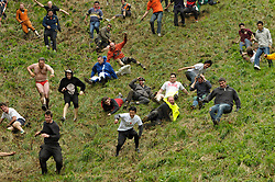 © Licensed to London News Pictures. 26/05/2014; Brockworth, Gloucestershire, UK.  The annual custom of Cheese Rolling down Cooper's Hill, with participants chasing a double Gloucestershire cheese down a very steep slope.<br /> Photo credit: Simon Chapman/LNP