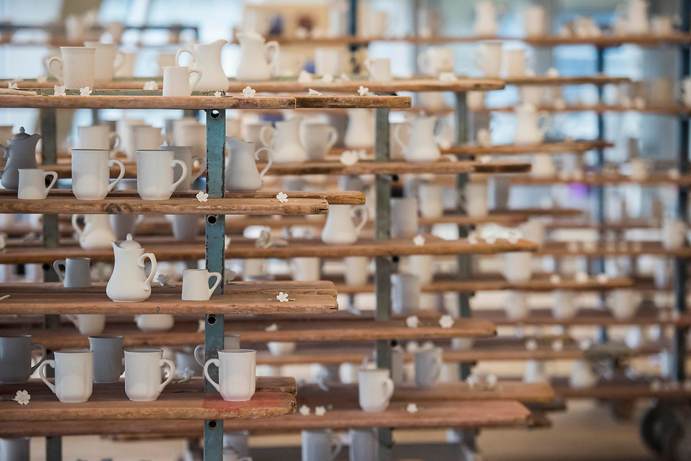 Racks of completed ceramics - FACTORY: the seen and the unseen an installation, in the form of a ceramics factory, by artist Clare Twomey. It is set up in the Blavatnik Building of the Tate Modern and launches the second year of Tate Exchange which, over 2017 and 2018, will focus on the theme of production.