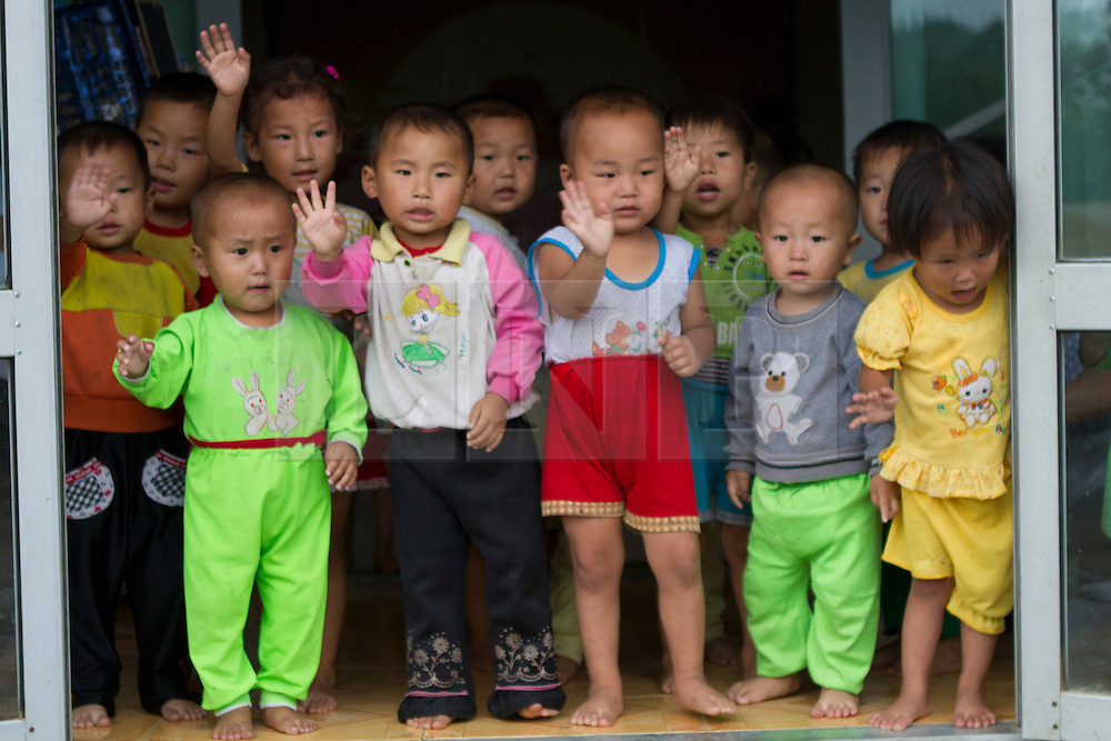 © Licensed to London News Pictures. 13/08/2011. Wonsan, North Korea. A group of North Korean pre-school children greet western tourists visiting the Chosan cooperative farm near Wonsan. Photo credit : James Gourley/LNP/