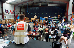 30 July 2021. Calais, France.<br /> Matt Cowling leads the morning briefing at British founded charity Care4Calais as they prepare to head out offering assistance in the form of food, phone charging, tents, blankets, tarpaulins and other vitally needed services to migrant refugees in Calais. With police ramping up efforts to make Calais as hostile as possible, it has become increasingly difficult for charities to help migrants, many of whom have taken to living in swampy inhospitable terrain spread around the town. <br /> Photo©; Charlie Varley/varleypix.com