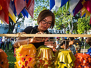 10 SEPTEMBER 2016 - BANGKOK, THAILAND: People hang traditional Thai paper flowers in Pom Mahakan during a community party in the old fort. The flowers are hung as decorations. Forty-four families still live in the Pom Mahakan Fort community. The city of Bangkok has given them provisional permission to stay, but city officials say the permission could be rescinded and the city go ahead with the evictions. The residents of the historic fort have barricaded most of the gates into the fort and are joined every day by community activists from around Bangkok who support their efforts to stay.                PHOTO BY JACK KURTZ