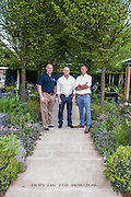 Actor Ross Kemp with the designer and Rory Mckenzie a wounded veteran (blue shirt) on the Hope on the Horizon garden.  The<br /> 'Hope on the Horizon' garden in aid of Help for Heroes: produced by building and landscaping firm Farr and Roberts', making their debut; designed by Matthew Keightley (29), as a result of his brother Michael's involvement with the armed forces, having served on four tours to Afghanistan and due for his fifth this year; and sponsored by the David Brownlow charitable foundation. The garden layout is based on the shape of the Military Cross, the medal awarded for extreme bravery. Granite blocks will represent the soldiers' physical wellbeing and the planting represents their psychological wellbeing at various stages of their rehabilitation. Both evolve through the garden from a rough, unfinished, over-grown beginning through to a perfectly sawn, structured end. An avenue of hornbeams draws the attention through the entire garden to a sculpture resembling a hopeful horizon; a reminder to the soldiers that they all have a bright future ahead. As well as areas to recline and reflect, the garden offers focal points all the way through. Cool, calming colours are used throughout, helping to emphasise the fact that it will be a serene, contemplative space. After the Show, the garden will be moved and set within the grounds at Help for Heroes Recovery Centre at Chavasse VC House in Colchester, Essex. The garden will offer a serene, peaceful haven to contemplate and inspire a bright future and to support the challenging journey to recovery. The Chelsea Flower Show 2014. The Royal Hospital, Chelsea, London, UK.  19 May 2014.