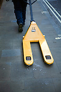 Man pulling yellow pallet truck along street pavement