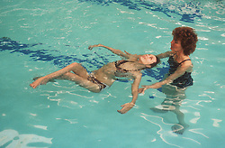 Carer supporting girl with disability in swimming pool,