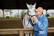 Mature man kissing a horse