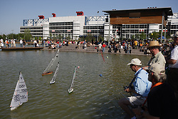 Stock photo of men racing their radio controlled sailboats on the pond