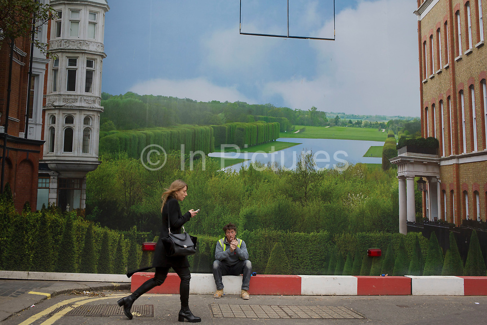 Hoarding outside a shop under refurbishment makes an interesting street scene on New Bond Street, London, UK. A weird visual juxtaposition is created as people integrate with the large scale printed photograph. A workman on a break watches as a woman passes.
