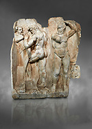 Roman Sebasteion relief sculpture of  Herakles is preparing to wrestle the Libyan giant Antaios. Aphrodisias Museum, Aphrodisias, Turkey. Against a grey background.<br /> <br /> Herakles (left) is taking off his bow case to hang it on a pillar statue. Antaios (right) is binding up his head with ear protectors, next to him stands an oil basin used in the palaistra (wrestling ground). Antaios was a famous wrestler who challenged and killed all visitors to his country, until he was defeated by Herakles. .<br /> <br /> If you prefer to buy from our ALAMY STOCK LIBRARY page at https://www.alamy.com/portfolio/paul-williams-funkystock/greco-roman-sculptures.html . Type -    Aphrodisias     - into LOWER SEARCH WITHIN GALLERY box - Refine search by adding a subject, place, background colour, museum etc.<br /> <br /> Visit our ROMAN WORLD PHOTO COLLECTIONS for more photos to download or buy as wall art prints https://funkystock.photoshelter.com/gallery-collection/The-Romans-Art-Artefacts-Antiquities-Historic-Sites-Pictures-Images/C0000r2uLJJo9_s0