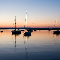 Sailboats in the Connecticut River after sunset in Old Lyme, Connecticut.