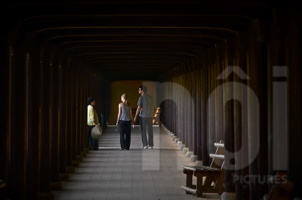 In one of the corridors of Hue citadel, a young Western couple is holding hands and listening to their guide. Vietnam, Asia