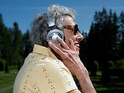 elderly woman listening to headphones. exterior day park setting