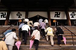 Visitors climb stairs into Zenko Ji Temple at Nagano in Japan